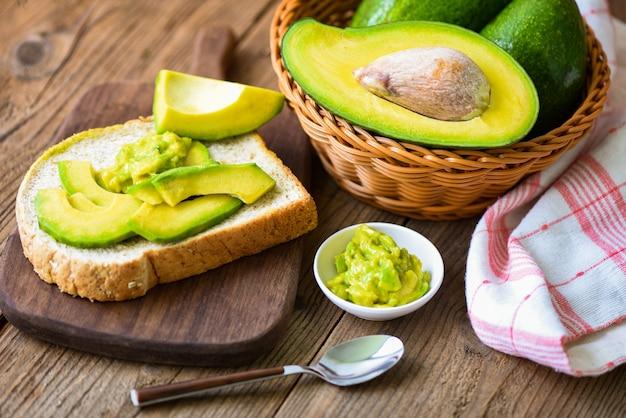 Frischer und reifer avocado-toast auf einem holztisch