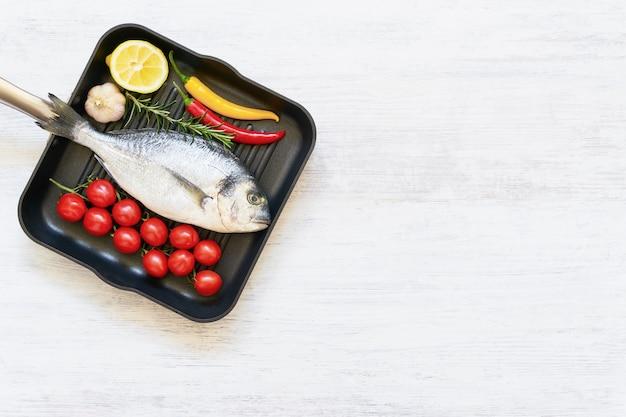 Frischer ungekochter dorado- oder seebrassenfisch mit gemüse in der pfanne auf weißem hintergrund