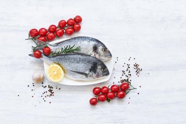 Frischer ungekochter dorado- oder seebrassenfisch mit zitrone, gemüse und gewürzen über weißem tisch. oben