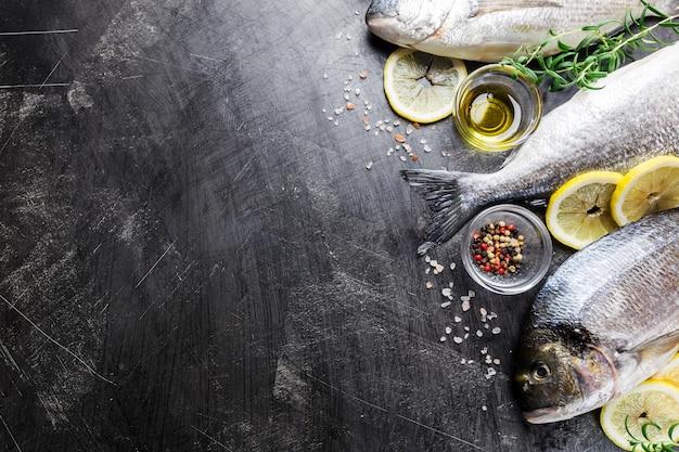 Frischer ungekochter dorado- oder seebrassenfisch mit zitronenscheiben, gewürzen und kräutern. mediterrane küche. draufsicht
