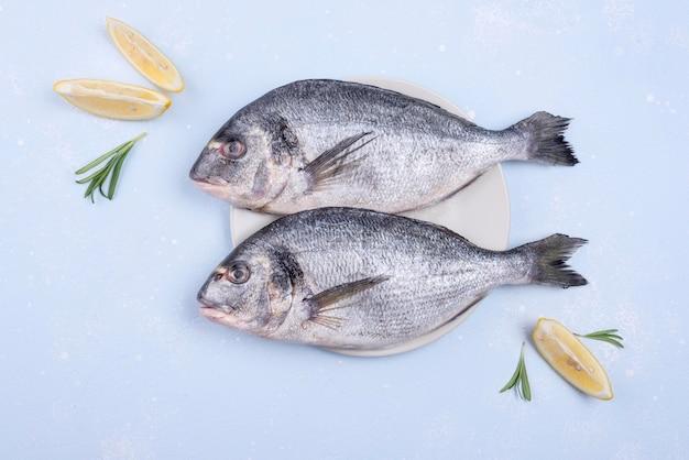 Frischer ungekochter fisch mit meeresfrüchten und zitronenscheiben