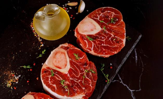 Frischer ungekochter geschnittener rindfleischschenkel in knochen und gewürzen auf schwarzem brett