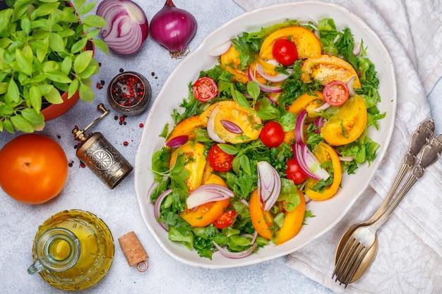 Frischer vegetarischer gemüsesalat von bunten tomaten
