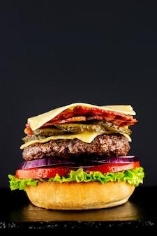 Frischer vegetarischer leckerer burger auf einem schwarzen hintergrund. einen bürger schrittweise machen