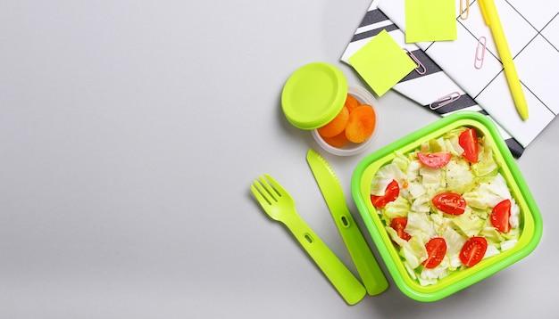 Frischer vegetarischer salat in der grünen brotdose mit plastikgabel und -messer am büroarbeitsplatz. schließen sie vom gesunden snack im plastikbehälter. gesundes nahrungsmittelkonzept. draufsicht, flache lage, grauer hintergrund.