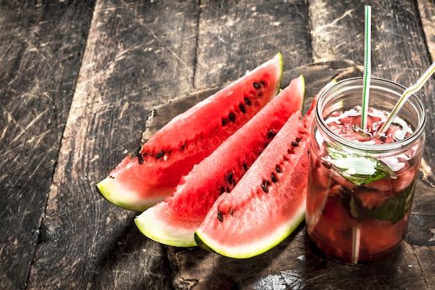 Frischer wassermelonensaft auf holztisch.