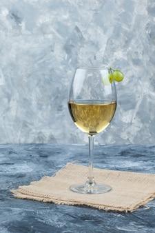 Frischer wein der seitenansicht im glas mit trauben auf gips und stück sackhintergrund. vertikal