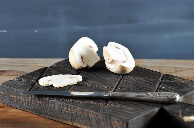 Frischer weißer pilzchampignon auf rustikalem hölzernem