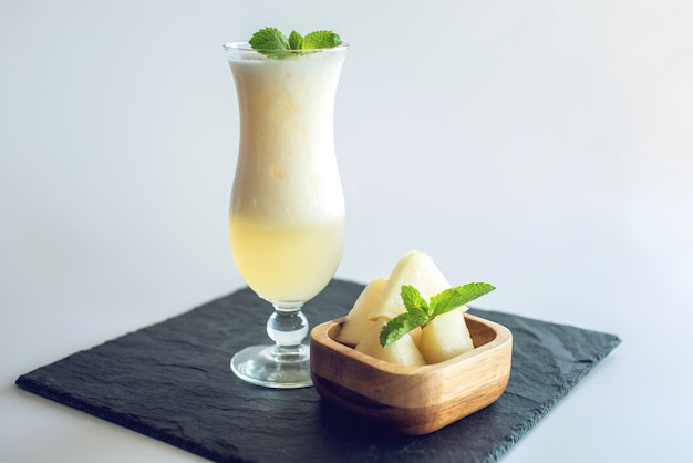 Frischer weißer smoothie in einem glas mit geschnittenen melonen- und minzstücken