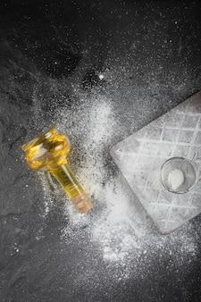 Frischer weizenboden verschüttet auf holzbrett mit glas öl