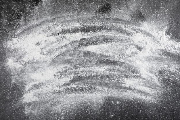 Frischer weizenboden verschüttet auf schwarzer oberfläche, ansicht von oben