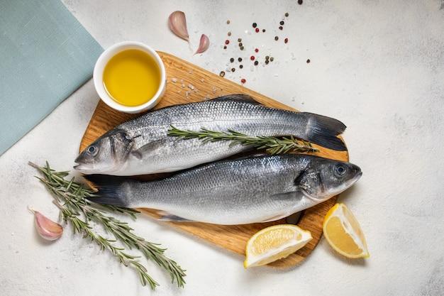 Frischer wolfsbarschfisch und zutaten zum kochen, zitrone und rosmarin. draufsicht des weißen hintergrundes.