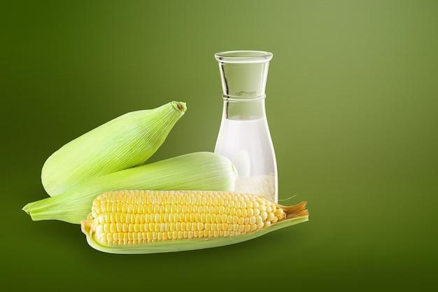 Frischer zuckermais und milch in der flasche auf grün