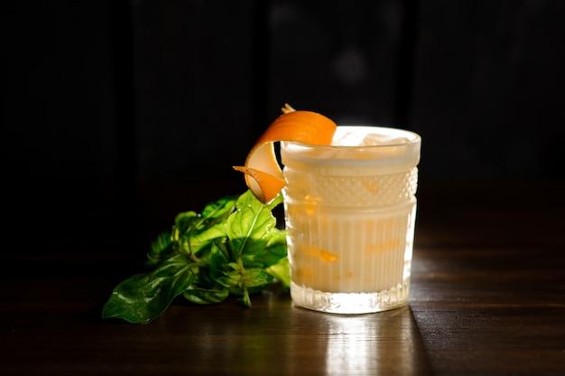 Frisches alkoholisches getränk in einem glas verziert mit orangenschale und basilikum