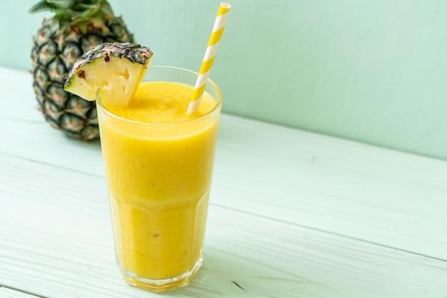 Frisches ananas-smoothie-glas auf holztisch