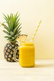 Frisches ananas smoothieglas auf hölzerner tabelle