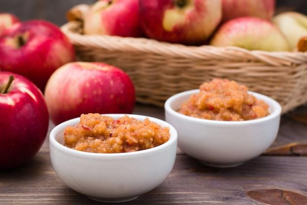 Frisches apfelmus in den schüsseln und in den roten äpfeln auf einem holztisch.