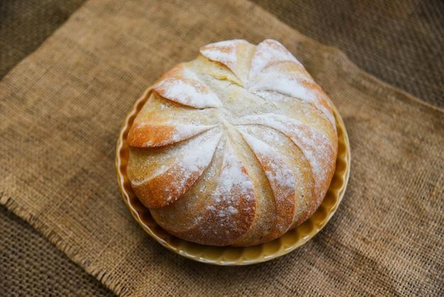 Frisches bäckereibrottablett auf dem runden brotlaib des selbst gemachten frühstücksnahrungskonzeptes des sackhintergrundes