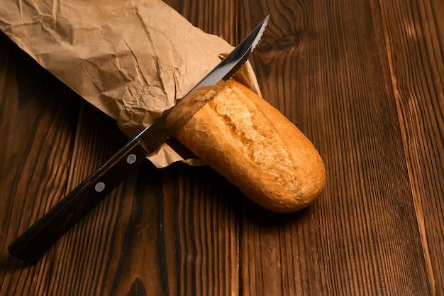 Frisches baguette in einem handwerkspaket-brotmesser auf brauner holzoberfläche