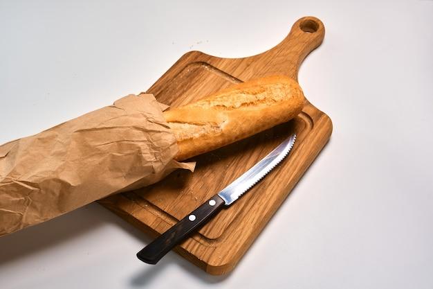 Frisches baguette teilweise in scheiben geschnitten und brotmesser auf einer hellen oberfläche