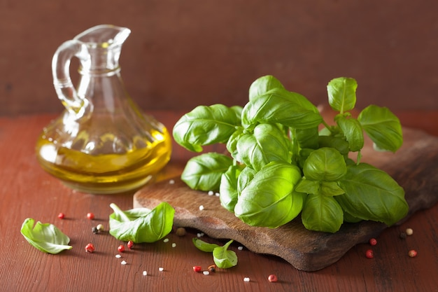 Frisches basilikum verlässt kräuter und olivenöl auf hölzernem bacgkround