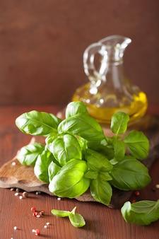 Frisches basilikum verlässt kraut und olivenöl auf hölzernem hintergrund