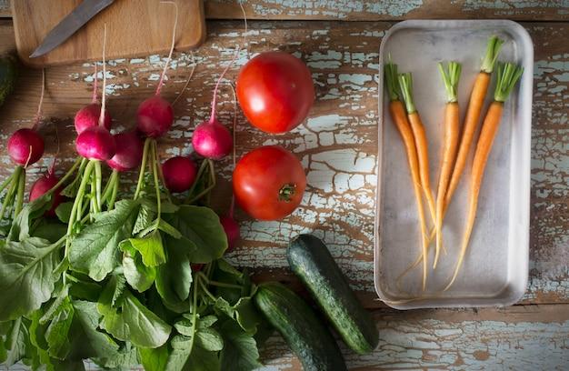 Frisches bauernhofgemüse - rettich, karotte, gurke und tomate auf alter hölzerner rustikaler draufsichtgrenze