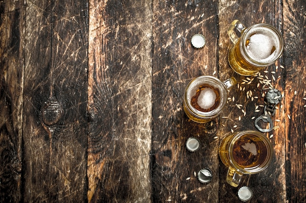 Frisches bier in einem glas mit stopfen und flaschenöffner. auf einem hölzernen hintergrund.