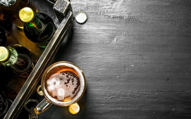 Frisches bier in einer alten schachtel auf schwarzer tafel.