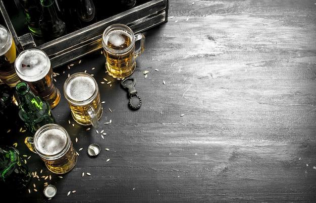 Frisches bier in gläsern und in einer alten schachtel auf schwarzer tafel.