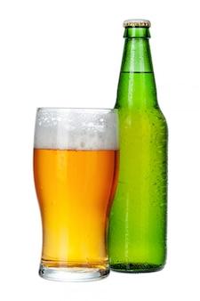 Frisches bierglas und flasche nah oben auf weißem hintergrund
