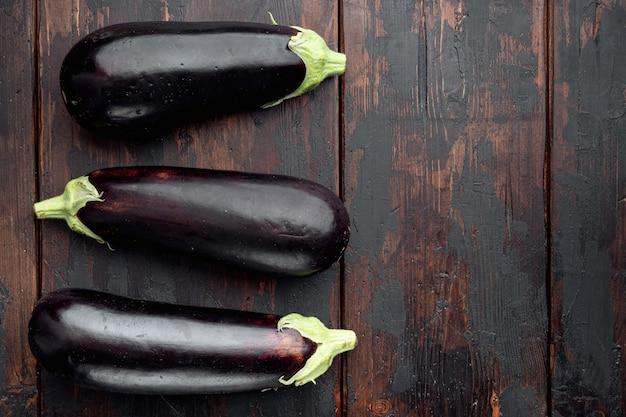 Frisches bio-auberginenset auf altem dunklem holztisch
