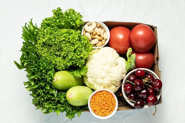 Frisches bio-bauerngemüse, obst und grün in papierbox auf weißer betonhintergrund-draufsicht.