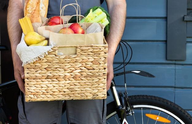 Frisches bio-brot, gemüse, gemüse und obst, müsli und nudeln in einem weidenkorb in den händen eines fahrradkuriers. fahrrad umweltfreundliche lieferung oder spende des ökologischen farm food konzepts.