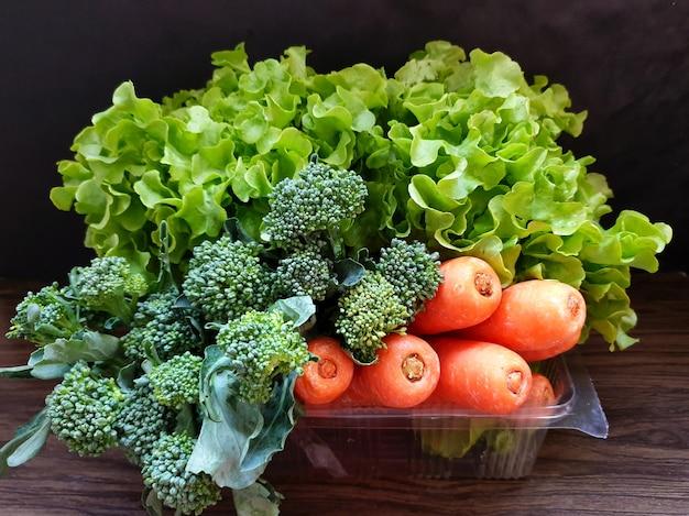 Frisches bio-gemüse auf holzuntergrund wie karotten-brokkoli-grüner salat