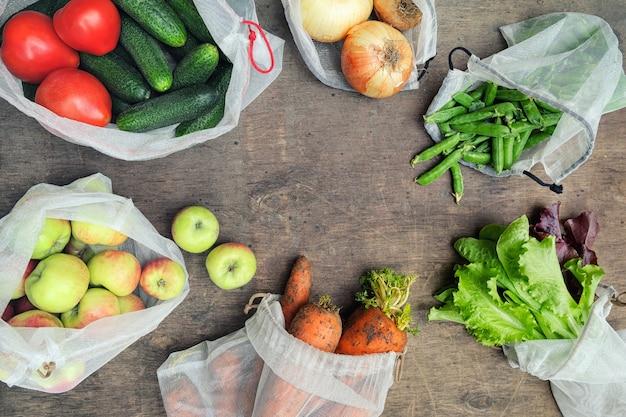 Frisches bio-gemüse, obst und gemüse in wiederverwendbaren recycelten mesh-taschen. zero waste shopping-konzept. kein einwegkunststoff.