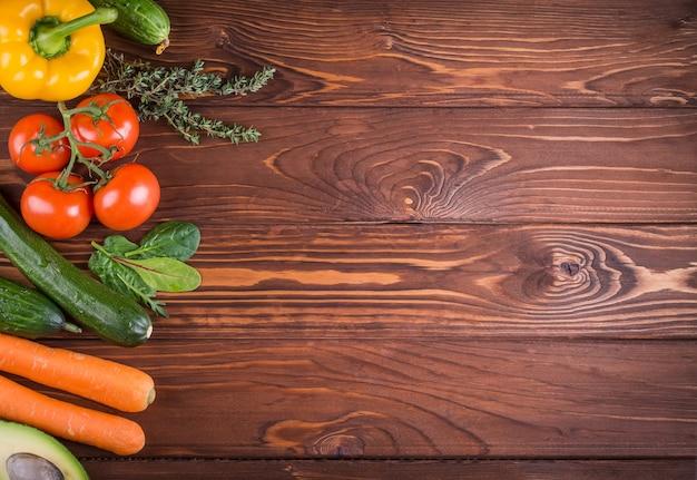 Frisches bio-gemüse. pfeffer, tomate, avocado, auf hölzernem hintergrund. gesundes essen und gesundes lebenskonzept. draufsicht.