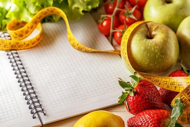 Frisches bio-gemüse und obst, leeres notizbuch und stift öffnen