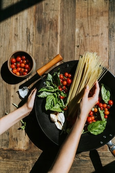 Frisches bio-gemüse und zutaten zubereitet in einer pfanne