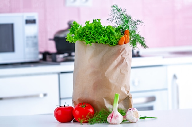Frisches bio-gemüse zum kochen gesunder diät-salat in der handwerklichen papiertüte auf dem tisch in der küche
