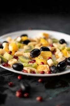 Frisches bio in scheiben geschnitten oder in kleine stücke geschnitten, exotische früchte, granat, kiwi, bananen