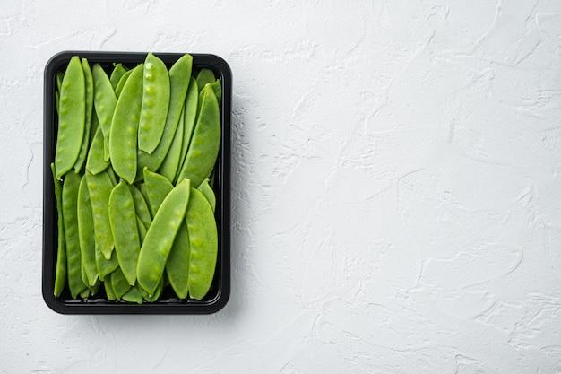 Frisches bio-mangetout, auch als zuckerschoten-set bekannt, in plastikbehältern auf weißem stein