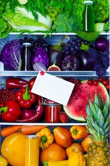 Frisches, biologisches, gesundes, rohes antioxidans, violettes, rotes, grünes, orangefarbenes und gelbes essen, gemüse, obst und säfte in veganem vegetarischem zustand öffnete den vollen kühlschrank mit vitaminen mit platz für text. gesundes essen.