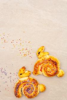 Frisches brötchen in form eines osterhasen. das konzept der kinderferienbäckerei. auf steinoberfläche kopieren sie raum, draufsicht.
