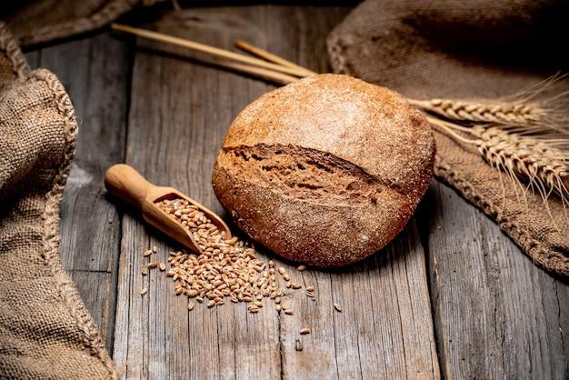 Frisches brot auf holzboden. frisch gebackenes traditionelles brot auf holztisch. gesundes essen