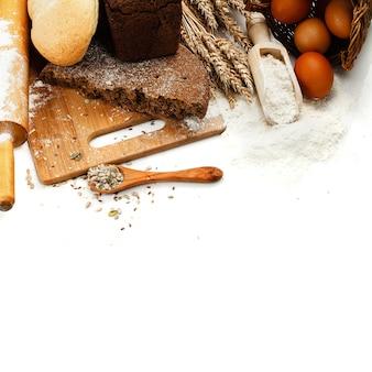 Frisches brot auf schneidebrett, schaufel mit blume und samen lokalisiert über weiß