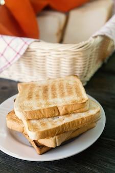 Frisches brot im korb. toast wird auf einer platte gestapelt.