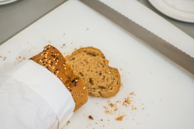 Frisches brot in scheiben schneiden und messer in buffet am schneidetisch.