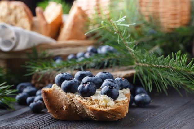 Frisches brot mit blaubeermarmelade und früchten auf einem rustikalen tisch