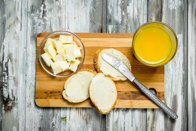 Frisches brot mit butter und orangensaft. auf rustikaler holzoberfläche